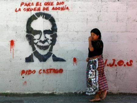 Mujer camina al lado de un grafitti que pide la condena de Ríos Montt en Guatemala. Fuente:laotraandalucia-org