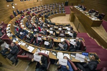 """Los diputados en Les Corts protestan contra la decisión exhibiendo carteles de """"RTVVnoestanca"""". Foto: EFE"""